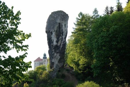 Rock of Hercules's mace with Castle on Pieskowa Skala in background, Eagles Nests trail. Medieval fortress in the Jura region near Cracow. Poland.