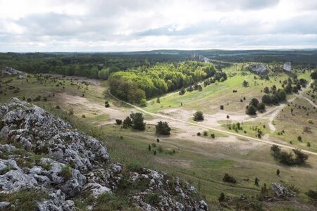 Beautiful view from rocky hill around Olsztyn castle - vast areas with forests lit by sun, Jura region, Cracow-Czestochowa Upland, Poland