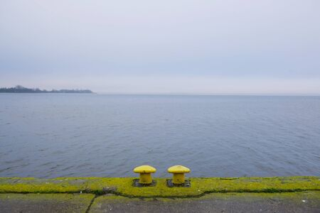Two yellow mooring bollards on empty dock by the lake off season in misty day. Kamien Pomorski, Poland Stockfoto