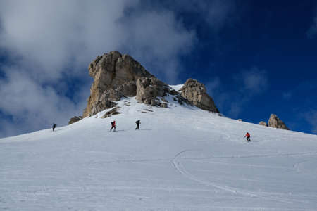 A group of skiers going on backcountry skis through snowy mountains on a sunny day. During trip in Dolomites around Tre Cime. Sexten Dolomites, South Tyrol, Italy