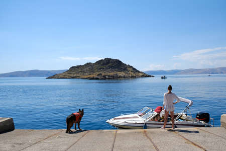 Idyllic view of a couple getting ready for a sea trip on a yacht. There is a dog on the shore in a life jacket. Island on horizon. Sveti Juraj, Croatia