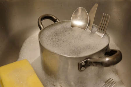 Cutlery put into old aluminum pot with foam during washing in the sink. Cutlery cleaning. Reklamní fotografie