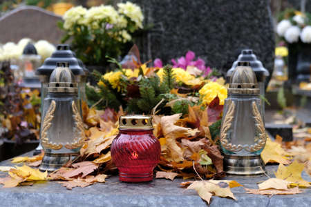 Colorful glass candles among dry autumn leaves on grave in cemetery on November day Stock fotó