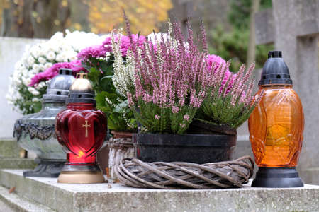 Colorful glass candles between autumn flowers in flower pots on grave in cemetery on November day