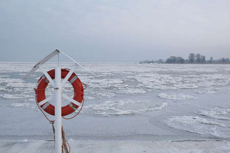 Lifebuoy on river covered with ice. Ice floe in shape of discs. An interesting phenomenon on Vistula river. The estuary of Vistula, Sobieszewska Island, Poland