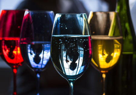 Upside down reflection of woman having drink by window. Colorful wine glasses with drinks and bottle on table. Standard-Bild