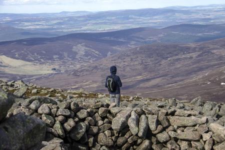 Hiker on the top of Mount Keen. Angus, Aberdeenshire, Scotland, UK Redakční