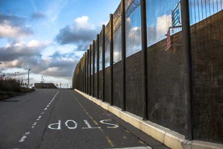 Prison walls and security fence with spikes on the blue sky background. Peterhead Prison Museum, Scotland, United Kingdom.