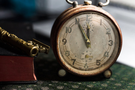 Old alarm clock, a book and metal key on a desk. Vintage background.