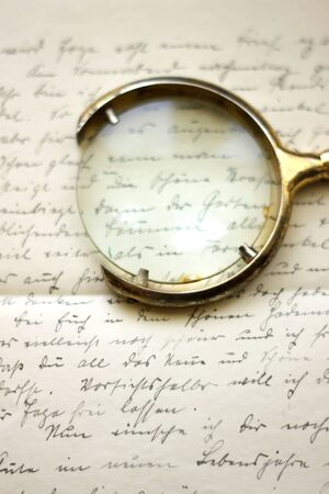 Old sheet of paper with handwritten text and a magnifier