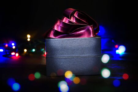 Luxury gift box with red ribbon and flashing lights. Christmas present on black background. Reklamní fotografie