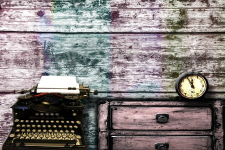Vintage, grunge style background with old typewriter and alarm clock on a cupboard with drawers