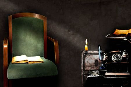 Vintage room decor with old chair, open book, antique telephone, inkwell with fountain pen and candle on a cupboard.