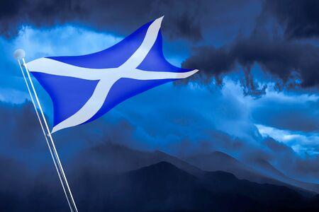 Scottish flag flutters in the wind on blue sky background