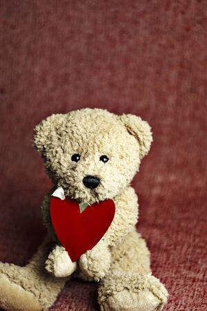 Netter Teddybär, der mit rotem Herzen sitzt. Karte zum Valentinstag.