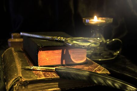 Old fashioned items on a table. Books, magnifier, feather pen and a candle.