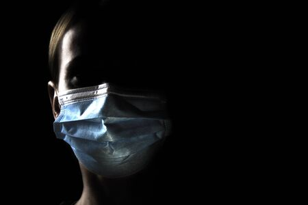 Close up portrait of a woman wear in medical protective mask. Coronavirus SARS-CoV-2 (Covid-19) prevention. Disease outbreak.