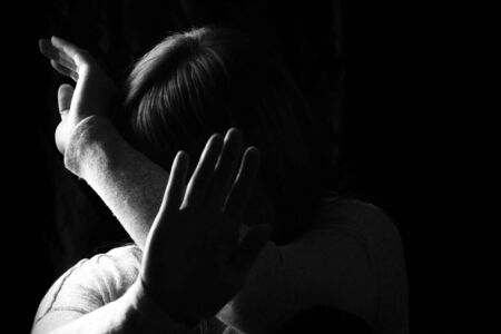 Black and white portrait of a woman showing gesture STOP. . Stop violence against women or mental health issue concept.
