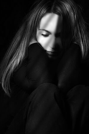 Portrait of a sad woman sitting in the dark Reklamní fotografie