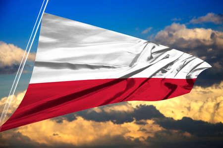 Polish flag waving against beautiful sky background.