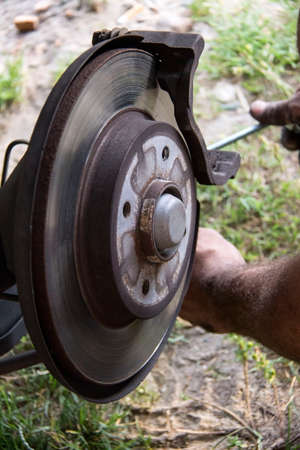 Mechanic repairs the brake pads in the car. Reklamní fotografie