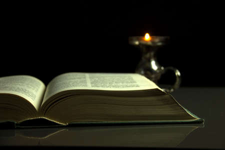 Open book in the dark and a candle