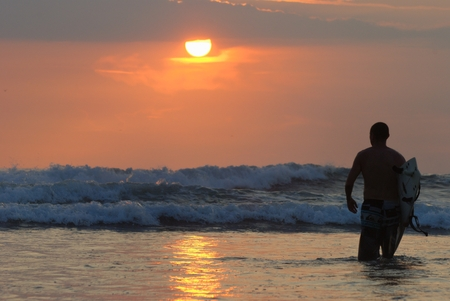 a surfer go to waves spot with nice sunset Stock Photo