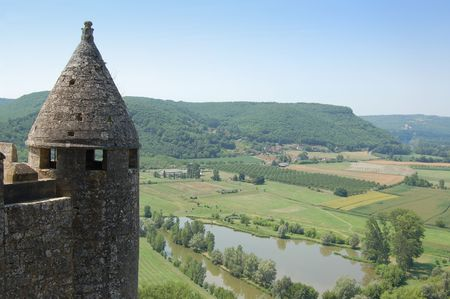 Dordogne river from the fortress of Chateau de Beynac, with part of the tower in the foreground. Horizontal composition photo