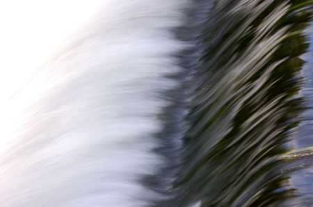 Water flowing over weir, taken  with slow shutter speed - horizontal composition photo
