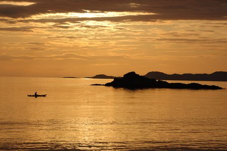 canoeist: A lone canoeist at sunset from the shoreline at Arisaig, Scotland