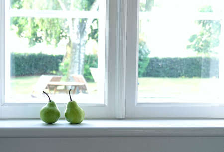 two, green pears on window sill