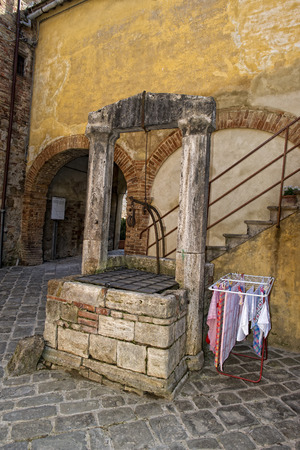 san quirico: Tuscany san quirico medieval houses with water well Stock Photo