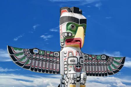 totem indien: Un poteau en bois de totem dans le fond bleu nuageux