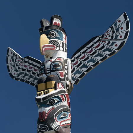 Isolated totem wood pole in the blue background photo