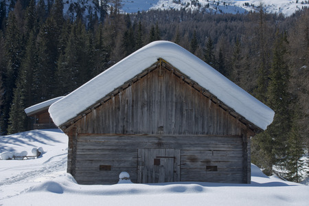 Old wood cabin house covered by snow