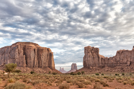 Monument Valley view at sunset with wonderful cloudy sky and lights on mittens photo