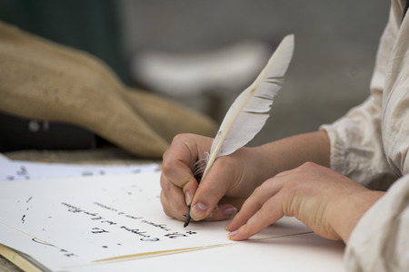 writing letter: hands while writing a letter with a plume
