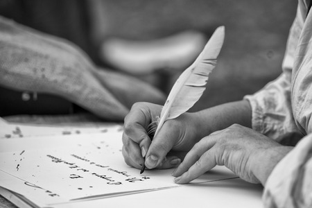 hands while writing a letter with a plume in black and white Stock Photo