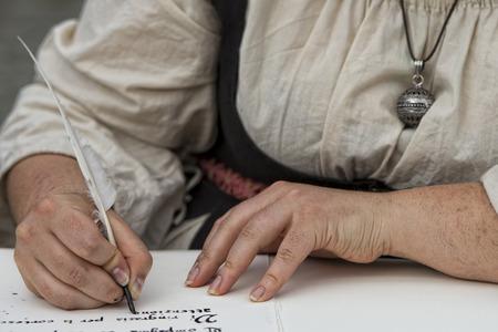pluma de escribir antigua: manos al escribir una carta con una pluma