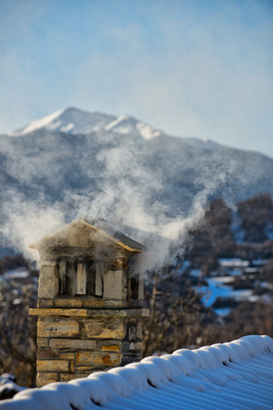 A mountain house roof with smoking chimney photo
