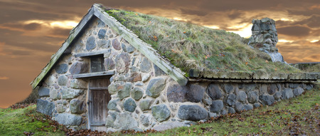 stone cabin with grass roof on sunset background
