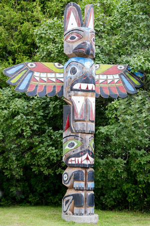 northwest indian art: Isolated totem wood pole in the green forest background Stock Photo