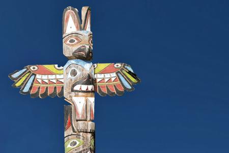 northwest indian art: Isolated totem wood pole in the blue background Stock Photo