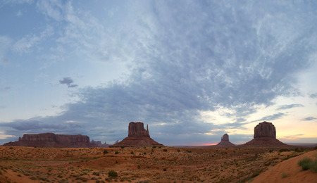 monument valley view: Monument Valley view at sunset with wonderfull cloudy sky and lights on mittens