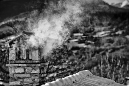 A black and white mountain house roof with smoking chimney photo