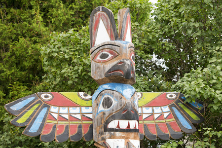 northwest indian art: Isolated totem wood pole in the forest background Stock Photo