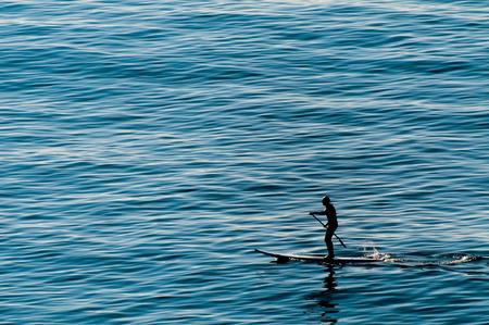tabla de surf: Un remo hombre de pie sobre una tabla de surf en el mar azul profundo
