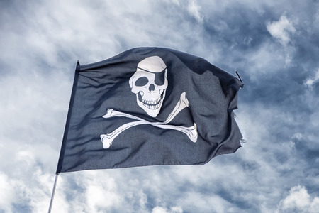 pirate banner: waving pirate flag jolly roger on sky background Stock Photo