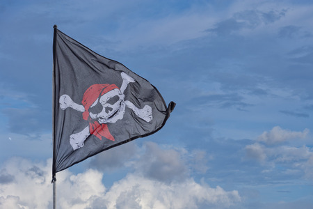 raise the white flag: waving pirate flag jolly roger on sky background Stock Photo