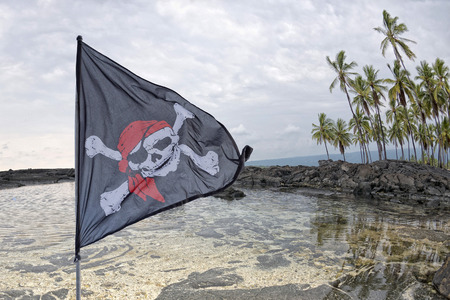 roger: waving pirate flag jolly roger on sky background Stock Photo
